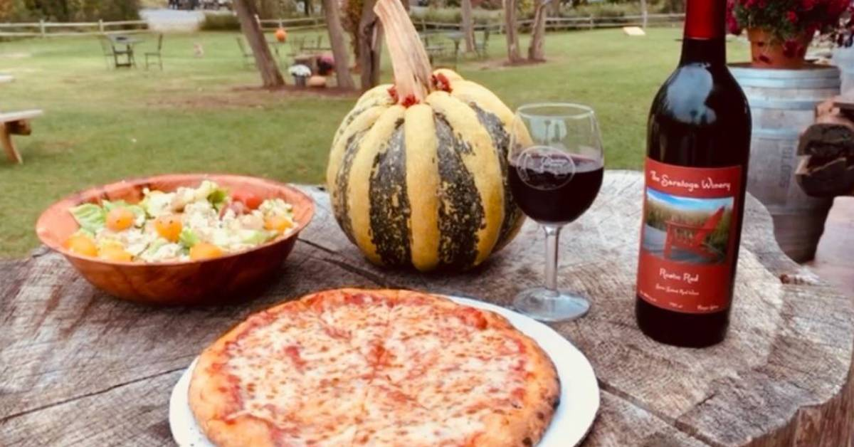 pizza, salad, wine bottle, wine glass, and squash on a wooden table outdoors