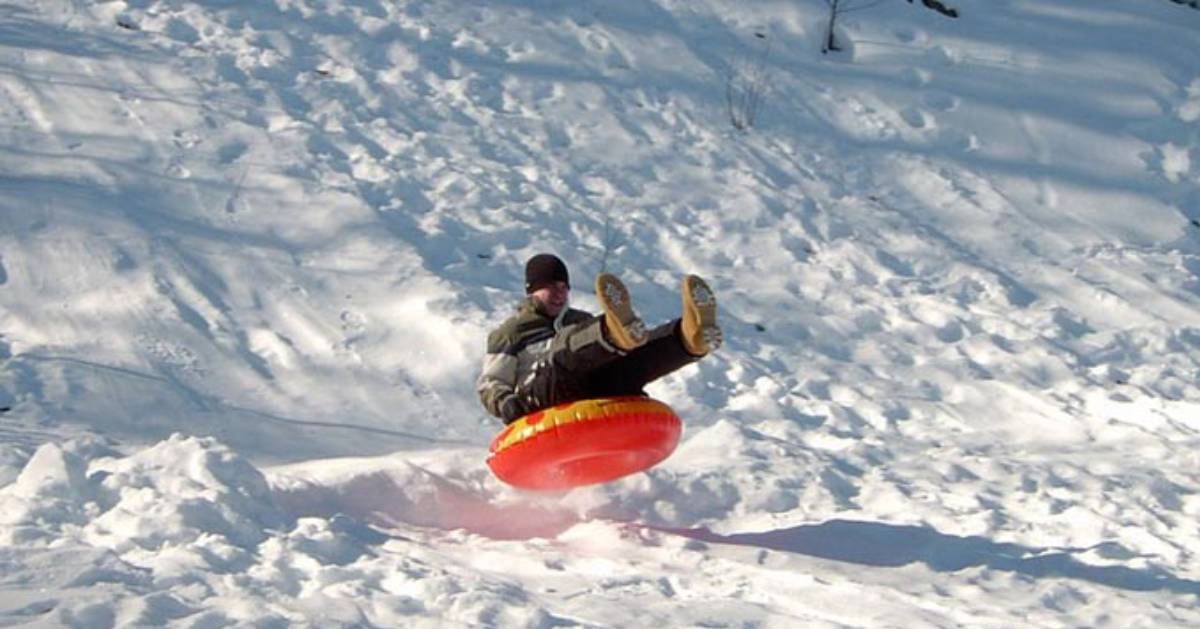 boy riding down an orange snow tube