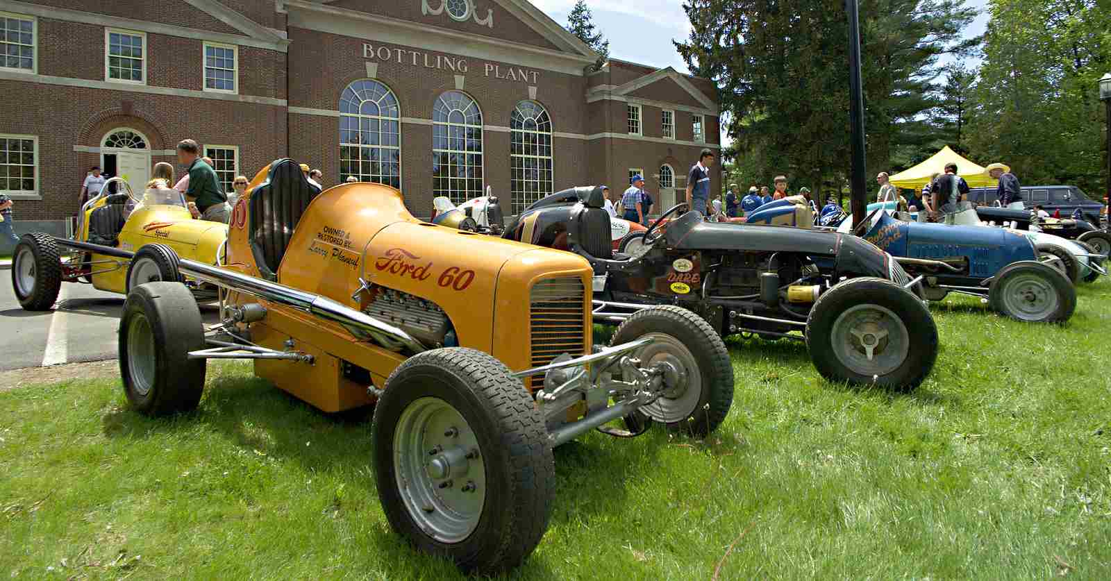 antique cars parked in a line in front of the saratoga automobile museum