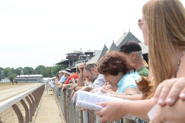 people watching a race from the rail