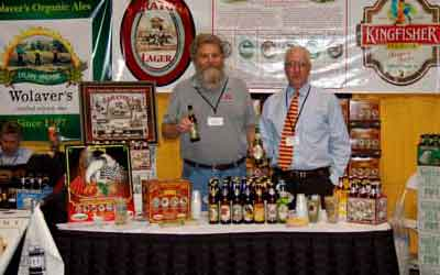 two men stand ebehind a booth of beers