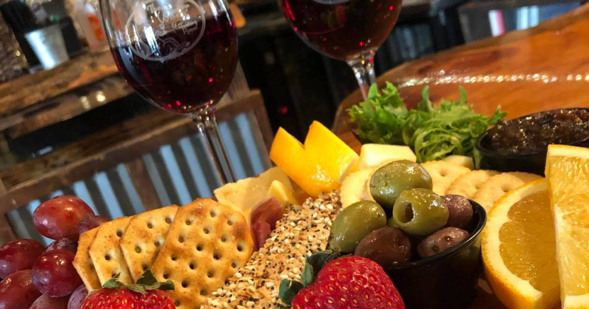cheese and cracker board with glasses of wine