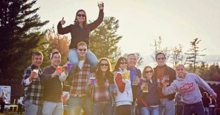 group of young people posing with their beers, a girl is ont he shoulders of one guy