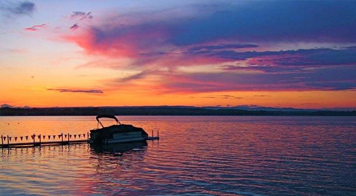 a pontoon boat on Saratoga Lake at sunset