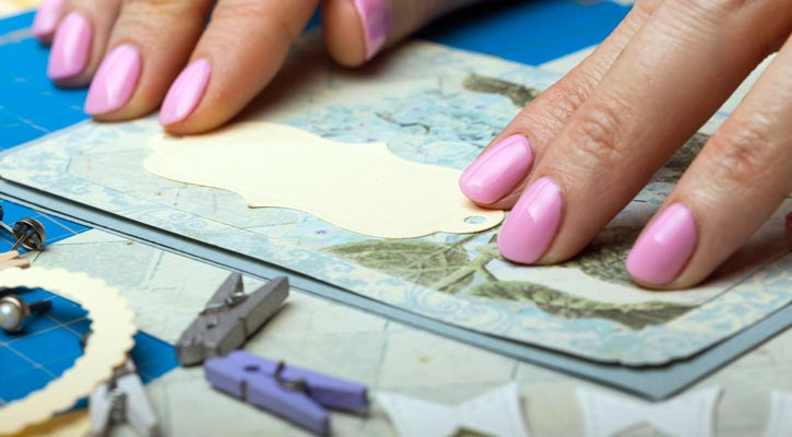 close up of a woman's hands with coral pink nailpolish as she puts together a scrapbook