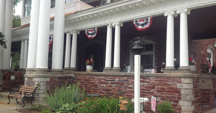 front of mansion with brick wall, bench, and American flags