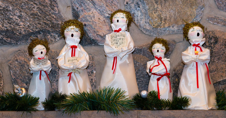 five figurines on a mantle singing