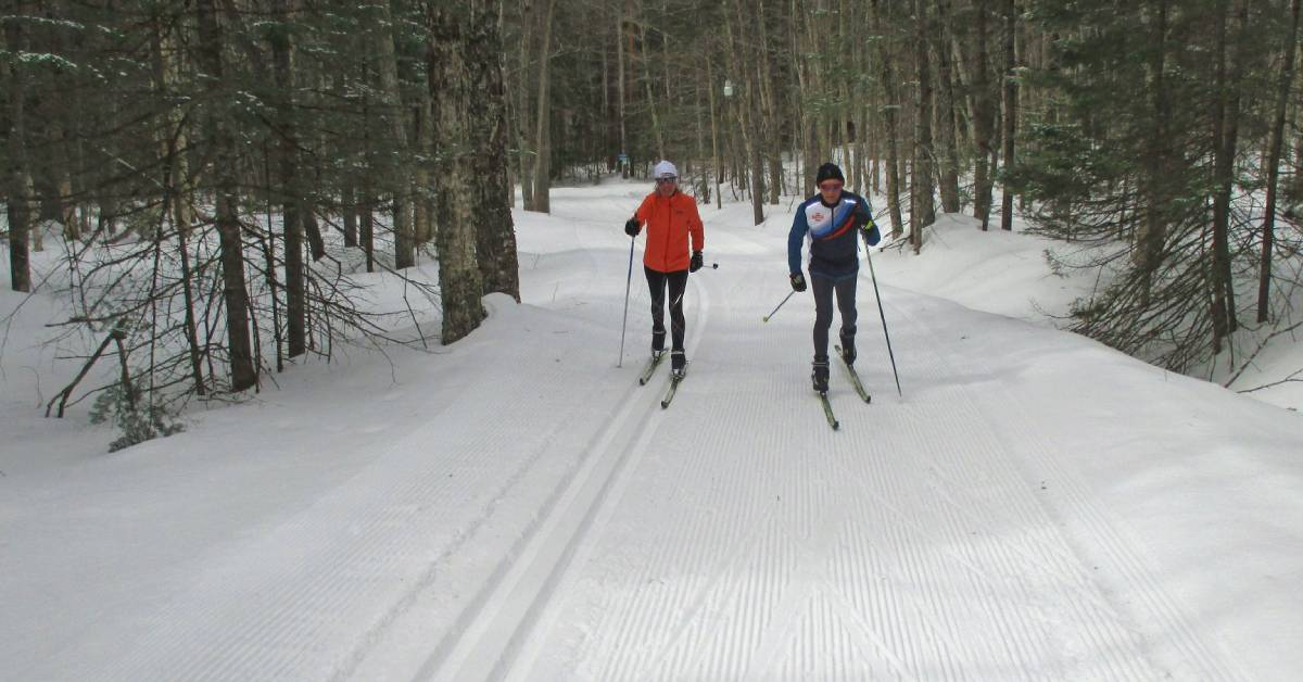 two cross country skiers on a groomed trail