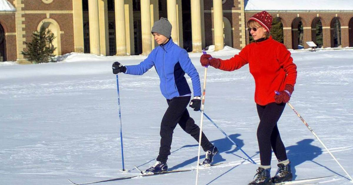 two cross country skiers, one with a red coat and the other with a light blue coat