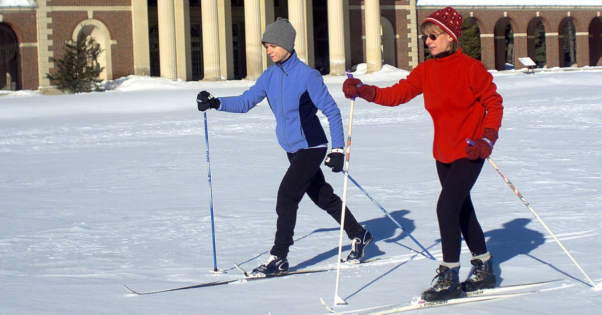 two people cross country skiing with building in background