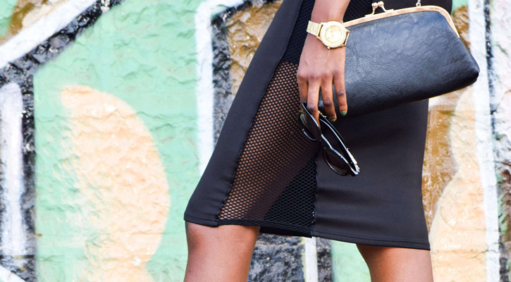 a woman's knee-length leather skirt, she's carrying a black purse and black sunglasses
