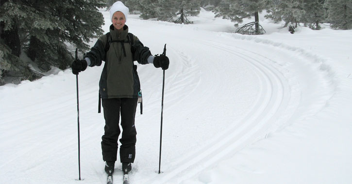 a woman cross-country skiing, stopping to pose while smiling