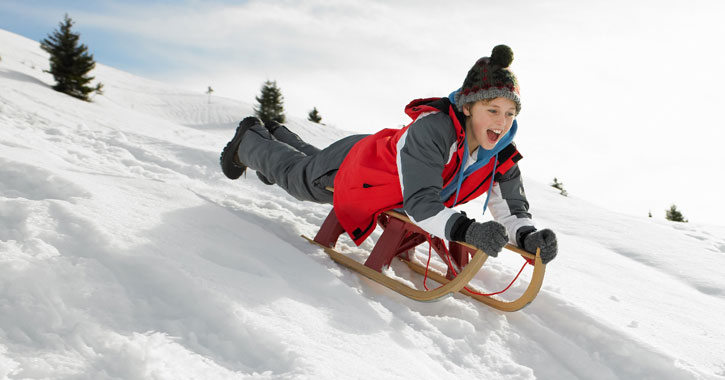 a young boy sledding down a hill on hi stomach, grinning