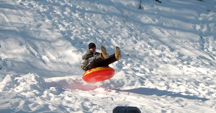 man going down snow covered hill in tube