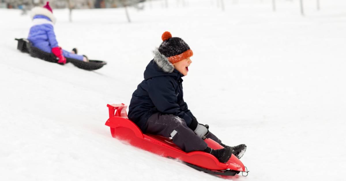 kids sliding down a snowy hill