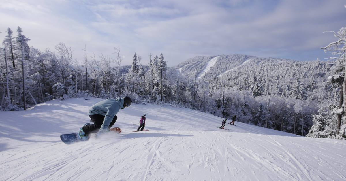snowboarders and skiers on a trail at gore mountain