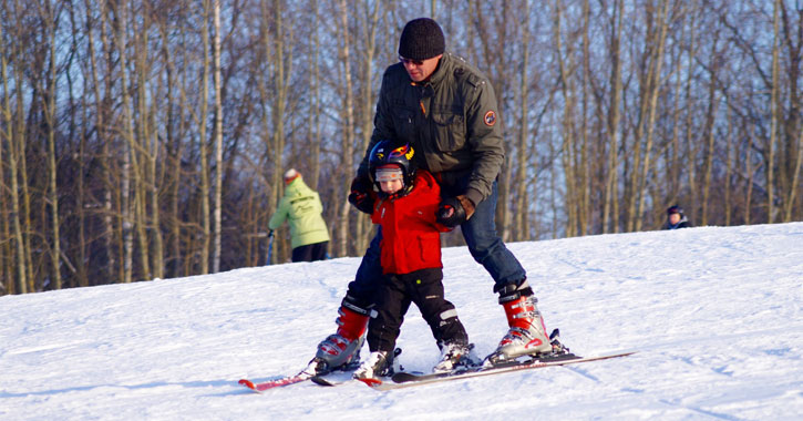 a man helping his son snowboard
