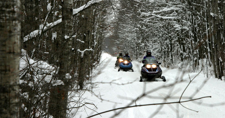 two people snowmobiling on a groomed trail through the woods