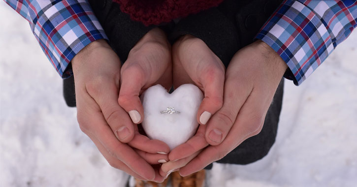 a couple's hands coming together to hold a heart-shaped piece of snow that has an engagement ring in it