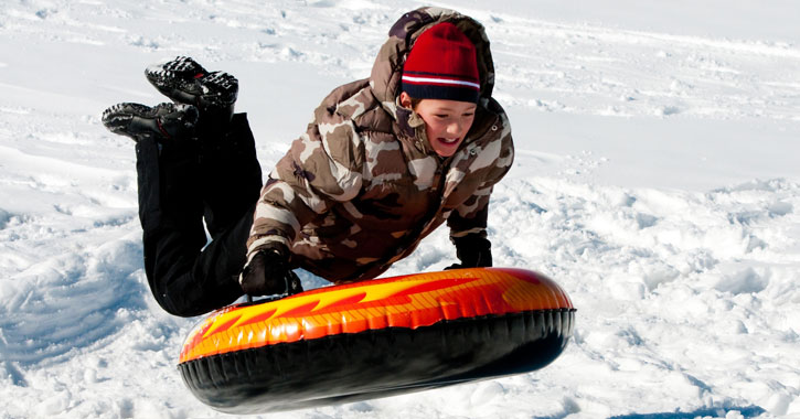 a young boy about to jump on a snow tube on his stomach