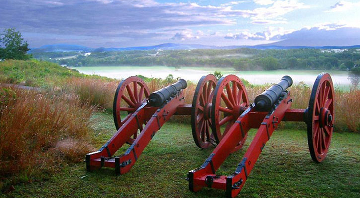 two cannons overlooking a view from the top of the mountain