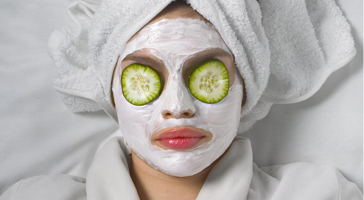 a woman lying down with a white towel wrapped around her head, a mud mask on her face, and cucumbers over her eyes