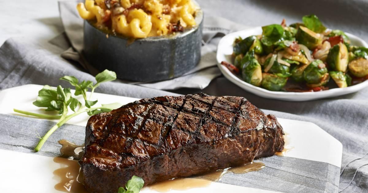 steak on a cutting board near food sides