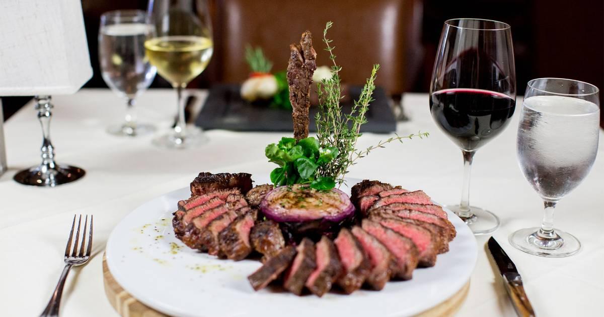 sliced steak on a plate near glasses of wine
