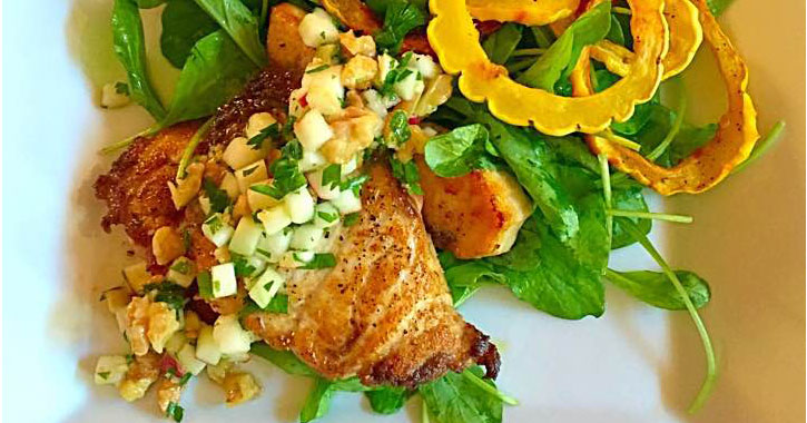 what looks like chicken with a mango salsa over a bed of greens