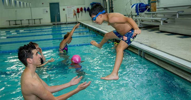 young boy jumping into a pool where a swim instructor is waiting