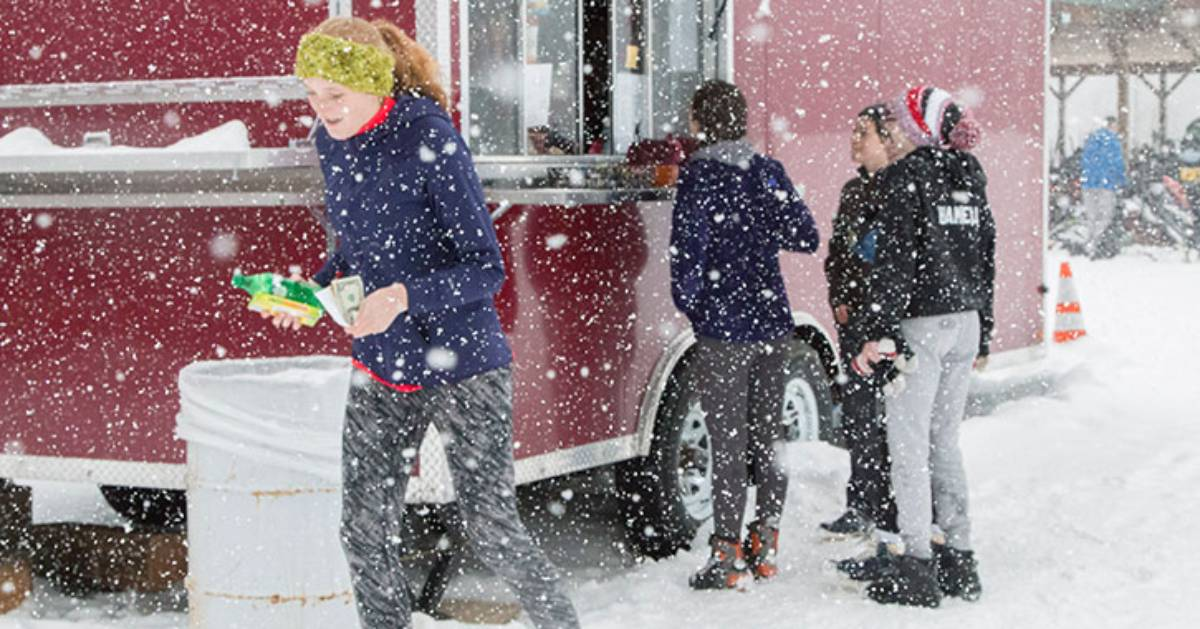 people by food truck on snowy day