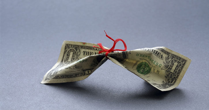 a red ribbon tied tightly around a dollar bill