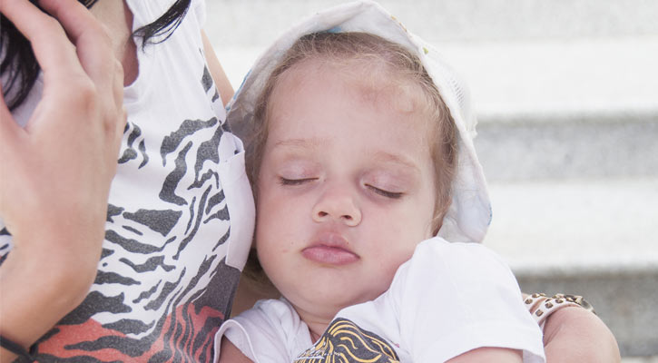 a young kid who has fallen asleep on his mom's lap