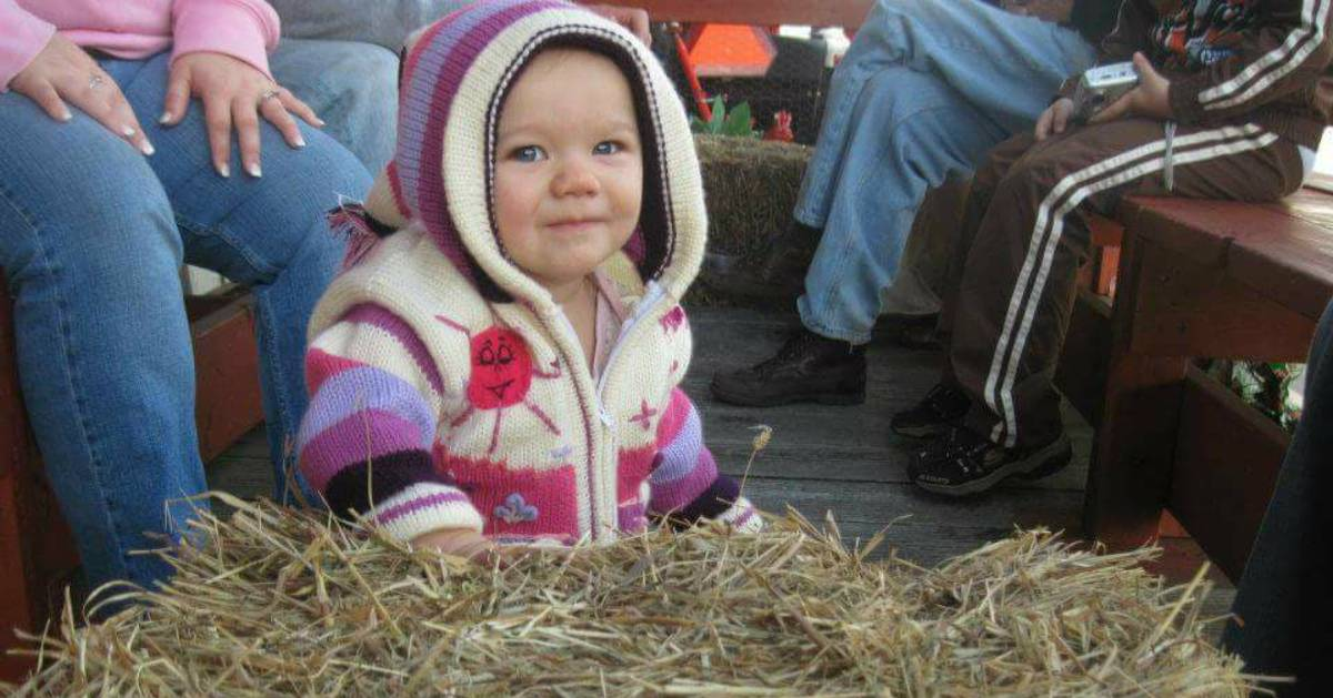 a toddler on a hayride with a pink striped sweater hoodie on