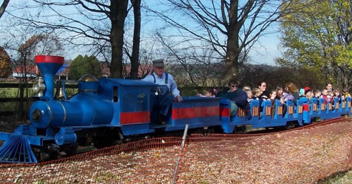 a blue train with people riding