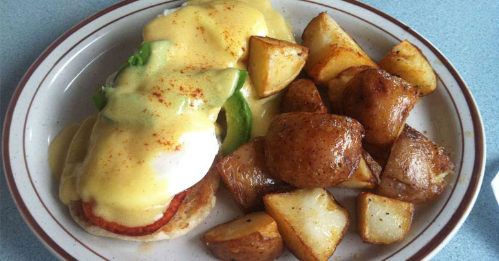 eggs benedict and breakfast potatoes on a plate