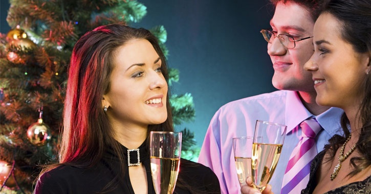 three people standing around Christmas tree with champagne