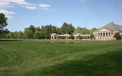 expansive green lawn with trees and building in background
