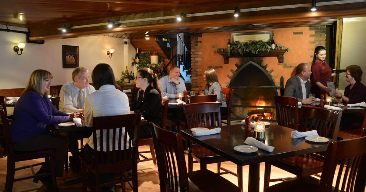people in a dining room with a fireplace going