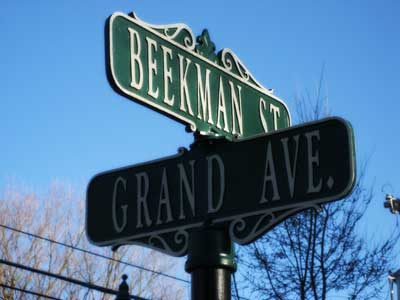 two street signs for Beekman St and Grand Ave