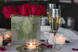 table set for a romantic dinner with roses and champagne