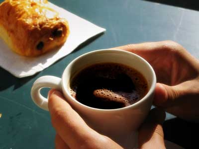 hands holding coffee with croissant
