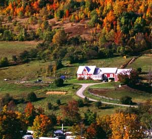 beautiful countryside with a large farmhouse surrounded by fall foliage