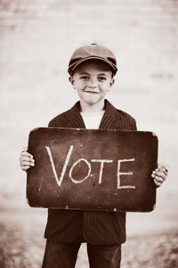 boy holding sign that says vote