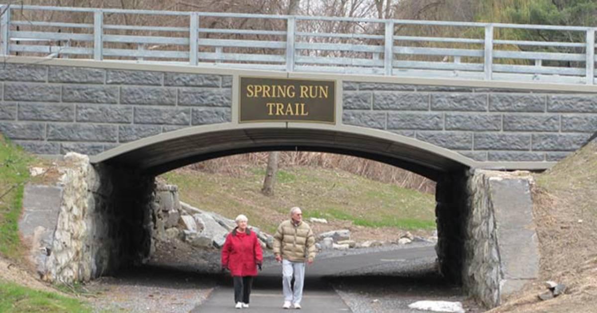 two people walking under bridge