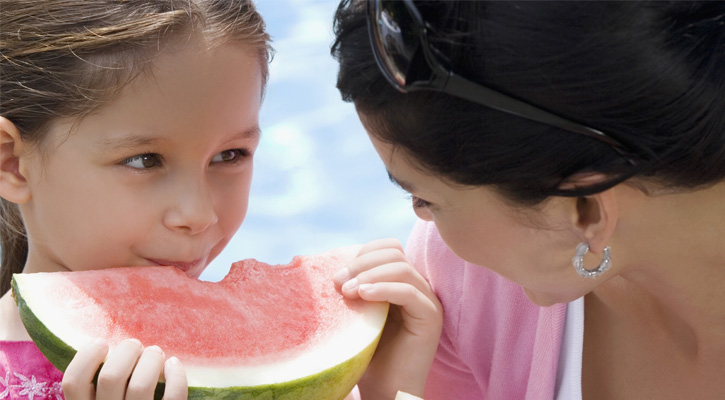 a girl eating watermelon and looking at her mother