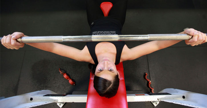 a view looking down on a young woman weight lifting