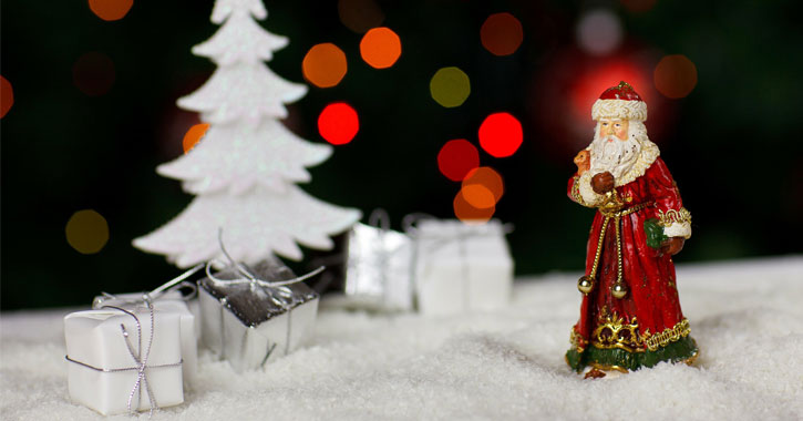 small Santa figurine on fake white snow with a small white Christmas tree and silver presents
