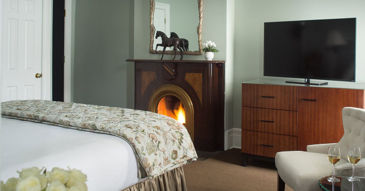 a fireplace in a hotel room near a tv and bed