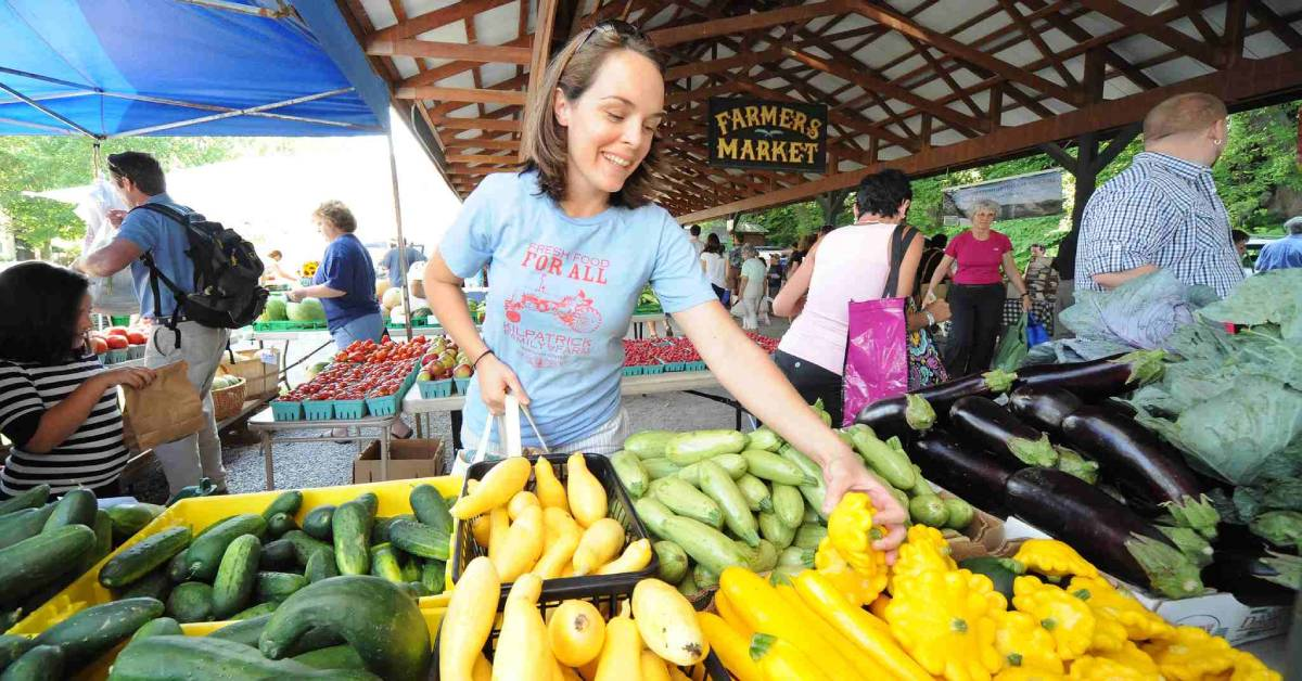 woman picking veggies at a farmers market